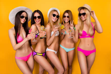 Smile for the camera! Five hot girlfriends are enjoying together at hen party near swimpool. Ladies are having drinks, posing, gesturing on bright yellow background, making memories of their funtime Stock Photo