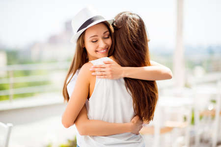Happy sisters hugging each other: love and care, trust and togetherness. They are in summer outside open air light terrace, wearing casual outfits, hat