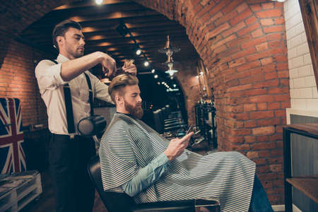 Side view of handsome young red bearded man browsing at his pda, while getting a haircut by classy dressed barber shop stylist