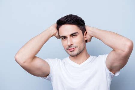 自信を持って笑みを浮かべて白い t シャツでハンサムな若い男。彼の完璧なヘアスタイルを固定、純粋な背景に立っています。だから、魅力的な過 写真素材