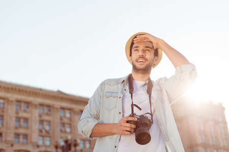 Check this out! What a view! Happy young tourist on vacation, in casual outfit, hat and with camera, on a sunny day outdoors