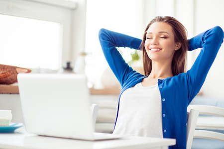 Young attractive lady is dreamy, resting with closed eyes in the cafe in front of laptop on white table. She is in casual outfit, smiling