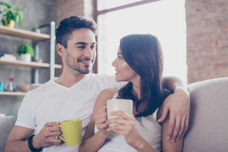 True love. Breakfast at the weekend together. Beautiful couple in casual outfit is sitting on sofa and smiling. They are drinking mugs of tea and look at each other with tenderness