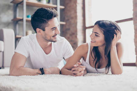 Together forever. A couple of young beautiful lovers are lying on the beige cozy carpet indoors at home, holding hands and looking deep into eyes of each other with love and tenderness Stockfoto