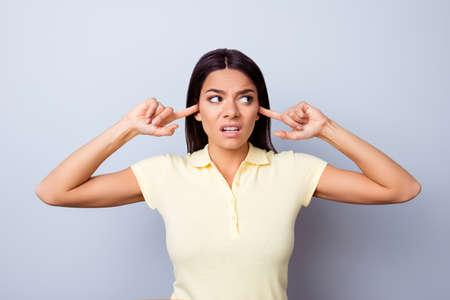 Annnoyed 若いラテン少女は、指で耳を閉じてのクローズ アップ。彼女は lookiing を離れて怒っている、彼女は純粋な背景にカジュアルな t シャツ 写真素材