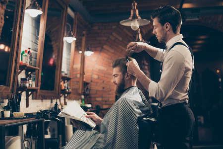 Faible angle de vue de profil d'un client de barbier élégant, barbu, qui se fait couper les cheveux d'un coiffeur élégant, lisant le magazine et attendant les résultats Banque d'images - 84622241