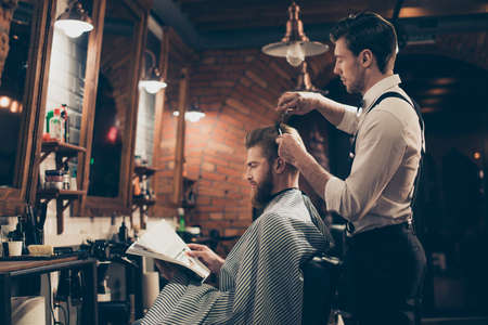 Low angle profile view of red bearded stylish barber shop client, which is getting his perfect  haircut from a classy dressed stylist, reading the magazine and waiting for result Archivio Fotografico