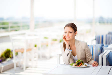 Dreamy cute young entrepreneur is waiting for her colleague for a business lunch at the open air light terrace of a roof top cafe, watching at the city view and smiling, wearing formal outfit