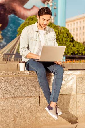 Brunete barbudo hermoso joven está navegando en su computadora portátil al aire libre en un día de verano. Muy elegante y moderno, con las piernas cruzadas, taza de café de plástico Foto de archivo - 84974605