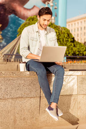 Young handsome bearded brunete is browsing on his laptop outdoors on a summer day. Very stylish and trendy, with crossed legs, plastic cup of coffee