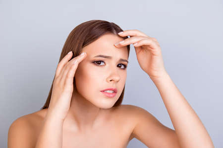 Aging, acne, pimple, wrinkles, oily, dry skin concept. Cose up cropped photo of pretty young lady touching her forehead and look serious and worried Stock Photo - 84608045