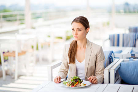 pedant: Pensive young business lady is having her lunch at the roof top restaurant`s open air light terrace, she is in a formal clothes and with pony tail, looking at the view of the summer city Stock Photo