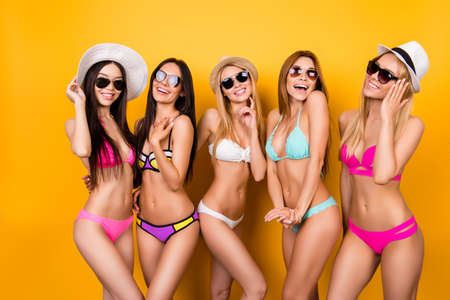 Summer, joy, hen party, playful mood. Five hot chicks are posing in trendy swimming suits and sunglasses, caps. They are protecting their healthy nice hair, skin and eyes from the strong sun