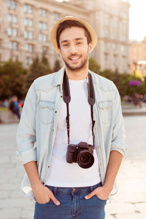 he: Young attractive guy is posing for photo of his summer holiday, outdoors in the town. He is in casual outfit, hat, with camera, hands are in the pockets of jeans