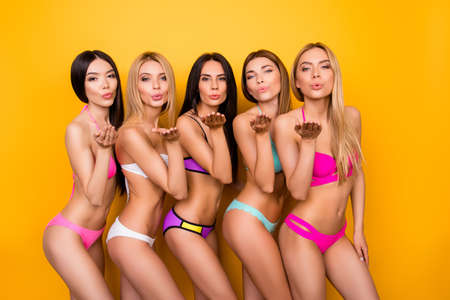 Air kiss for you from five hot ladies in fancy colorful swim wear, standing in tempting poses. So hot, sensual, perfect, ideal bodies and figures! Summer, diet, joy and health concept Фото со стока
