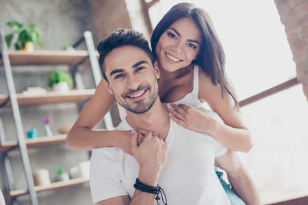 Love forever. Beautiful couple of young hispanic lovers are hugging with tenderness indoors at home, wearing white casual clothes Stock Photo