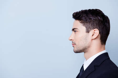 Side profile photo of a young handsome brunete realtor with bristle in a formal wear, standing on the pure blue background next to copyspace