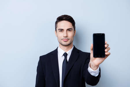 Handsome young guy finance broker with stubble is holding phone with black screen. He is wearing formal wear and a tie, stands on a light background Фото со стока