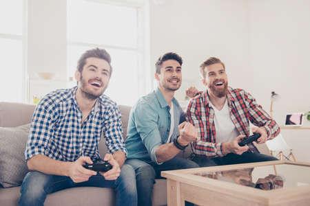 누가 이길 것입니까? 자동차 경주를하는 사람들의 경쟁입니다. 흥분된 친구들은 집에서 실내에서 게임을하고, 아늑한 베이지 색 소파에 앉아 즐기고
