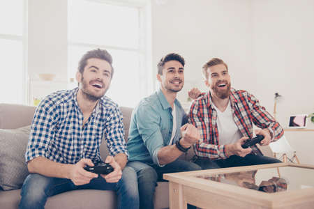 Who will win? Competition of guys playing car race. Excited friends are playing games  indoors at home, sitting on cozy beige sofa and enjoying themselves. They have great and fun time