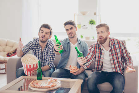 Upset young bearded guys are frustrated about the loss of the team in game they are watching. They are fans of sports games as football, basketball, hockey, baseball Stock fotó