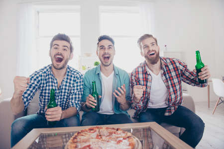 Goal! Cheerful young guys are watching match on couch at home and drink beer, eat pizza on the sofa at home indoors. They are fans of sports games as football, basketball, hockey, baseball