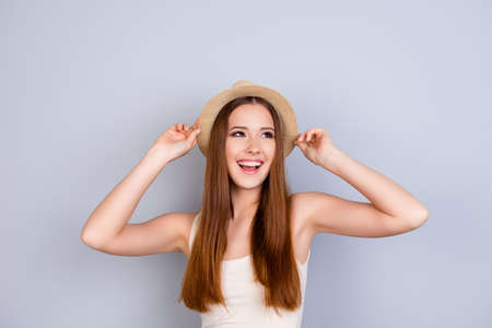 Happy young girl on summer vacation. She is in a stylish hat, wearing casual singlet, holding her beige cap, amazed, on pure light background