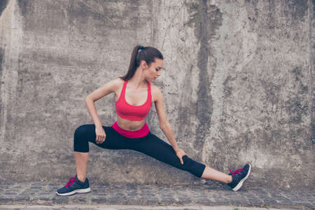 Young fashionable sportswoman is stretching on the street on a summer day. She is very bendy and flexible as a result of her regular trainings, wearing trendy sport outfit, shoes