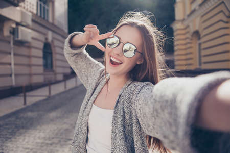 Cute young smiling girl is making selfie on a camera while walking outdoors. She is wearing casual outfit, mirror glasses