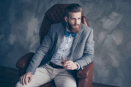 성공적인 젊은 빨간 수염 된 우아한 사업가 완벽 한 헤어 스타일와 소송에서 실내 위스키를 마시는, 휴식, 가죽 팔을의 자에 앉아, 가혹한 하 고 virile 스톡 콘텐츠