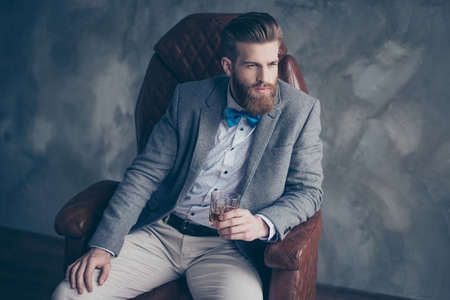 Successful young red bearded elegant businessman in suit with perfect hairstyle is drinking whiskey indoors, relaxing, sits on leather arm chair, looks harsh and virile