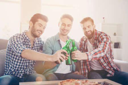 Close up of three happy friends, clinking their beers, smiling, all are in casual outfits. They are fans of sports games as football, basketball, hockey, baseball Stock Photo