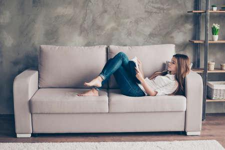 집에서 거실의 아늑한 베이지 색 소파에 누워 편안한 아가씨가 공부하고 있습니다. 멋진 현대적인 인테리어로 공부와 일하기에 편안한 분위기입니다.