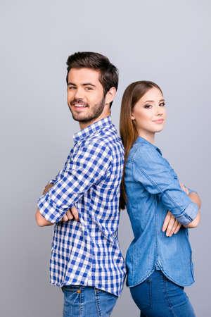 Twee vrolijke jonge geliefden kijken naar de camera en glimlach, staan rug aan rug, dragen vrijetijdskleding, met gekruiste handen op de zuivere achtergrond Stockfoto - 85642311