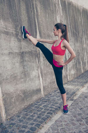 Young fashionable sportswoman is stretching on the street on a summer day. She is very bendy and flexible, doing nice flexible position, wearing trendy sport outfit, shoes