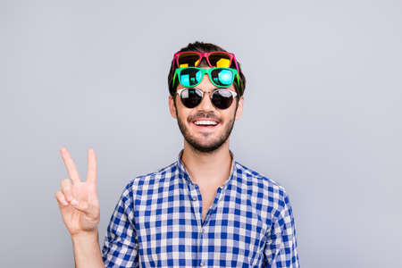 Playful young brunette bearded man in three pairs of bright colorful glasses and checkered casual shirt is fooling around, posing and shows v sign, smiling on light background