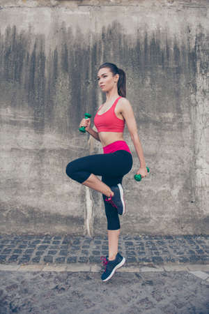 Young sportgirl is doing her cross fit workout outdoors, in modern pink and black sport wear and sneakers, using green dumbbells