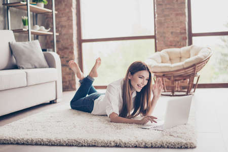 Young cheerful lady is waving to the camera while having video call lying on the carpet at home, so happy and excited