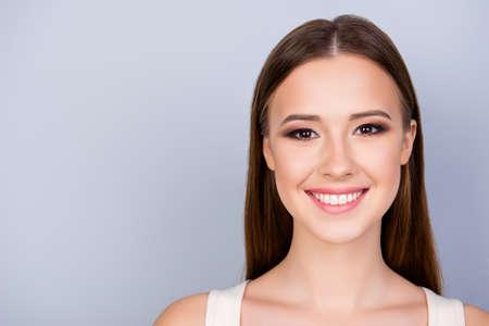 Gros plan sur la photo recadrée d'une jeune femme charmante et charmante sur le fond bleu clair, sourit à pleines dents, vêtu d'un simple maillot blanc