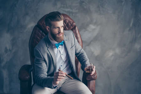 Portrait of handsome elegant young red bearded man holding glass of cognac and a cigar, sitting and resting in a formal wear in leather arm chair, so harsh, sucessful and rich! Stock fotó - 85642435