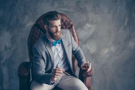 Portret van knappe elegante jonge rode bebaarde man met een glas cognac en een sigaar, zitten en rusten in een formele slijtage in lederen fauteuil, zo hard, sucessful en rijk!
