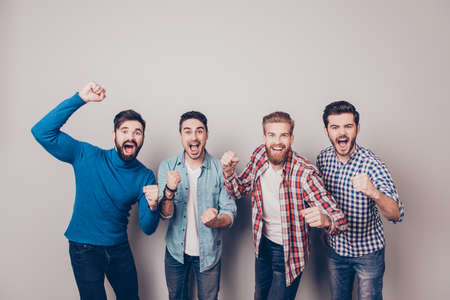 Four amazed young men are standing and gesturing for the victory on pure background in casual outfit and jeans.