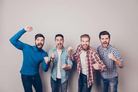 Vier verblüffte junge Männer stehen und gestikulieren den Sieg auf reinem Hintergrund in lässiger Ausstattung und Jeans. Standard-Bild