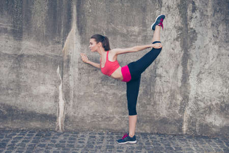 Young fashionable sportswoman is stretching on the street on a summer day. She is very bendy and flexible, doing nice yoga position, wearing trendy sport outfit, shoes