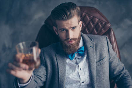 Cheers, ladies and gentlemen! Stylish elegant red bearded aristocrat in suit and bowtie holds glass with brandy, relaxing, sits on leather brown arm chair indoors