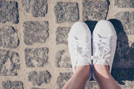 路上で外の天然色に白いガムの靴で若い女性の足のクロップショットを閉じます。