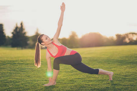 Young sport woman trainer is making stretching outdoors in spring park, so relaxed and healthy, wearing modern pink and black sport outfit, with pony tail