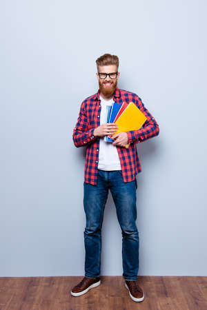 Cheerful young nerdy red bearded student standing with books on pure background in glasses and casual outfit Stock Photo