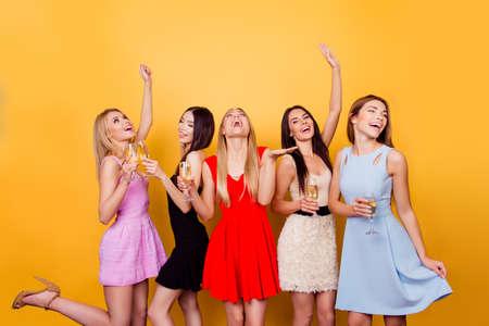 Vijf enthousiaste vriendinnen roosteren, allemaal in kleurige jurken, zo verbaasd, feestelijk, dansend en met plezier, kopie ruimte
