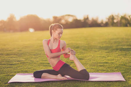 Young yoga trainer is making stretching sitting outdoors in spring park on a purple mat on nice green grass, so relaxed and healthy, wearing modern pink and black sport outfit, with tail